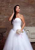 Brunette bride posing in studio with flowers Stock Photo