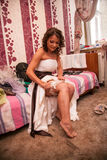 Brunette bride putting on lace garter Royalty Free Stock Photos