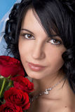 Brunette bride with red roses Royalty Free Stock Images