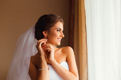 Brunette bride smiles while adjusting her earrings Royalty Free Stock Photography