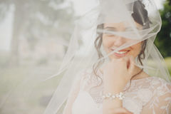 Brunette bride smiles sicncerely being hidden under a veil royalty free stock image