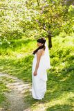 Brunette bride walking on path under trees at park Royalty Free Stock Images