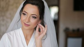Beautiful Bride with Earrings. Brunette bride wears white robe and veil sets earrings in the room stock video