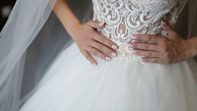 The Wedding Dress. Brunette bride wears white robe and veil sets earrings in the room stock video
