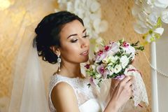Brunette bride with wedding bouquet. Beautiful bride looks at the wedding bouquet stock image