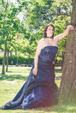 Brunette bride woman wedding blue dress near tree. A brunette bride woman is standing near a tree on a green lawn. She wears a wedding dress dark blue with wide Royalty Free Stock Images