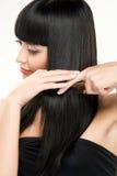 Brunette brushing hair Royalty Free Stock Images