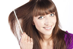 Brunette brushing her hair, in studio Royalty Free Stock Photography