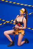 Brunette Builder On A Blue Background With An Electric Tool In The Hands Of Royalty Free Stock Image