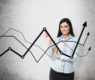 Brunette business lady presents a line graphs, which symbolise fluctuation of the business process. Royalty Free Stock Photo