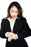 Brunette business lady on white background. A woman dressed in a business suit, she looks at hours on a hand Stock Images