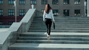 Brunette business woman climbs up the stairs stock video footage