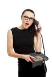 Brunette  businesswoman in black dress holding telephone and tal Royalty Free Stock Photos