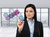 Brunette businesswoman is drawing a jigsaw puzzle on the glass screen. Stock Image