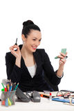 Brunette businesswoman putting on her make-up at work Royalty Free Stock Images