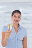 Brunette businesswoman raising a flute of champagne Stock Image
