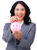 Brunette businesswoman saving money in a piggybank. Against a white background Royalty Free Stock Photo