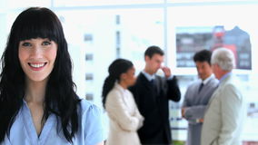 Brunette businesswoman standing in front of her team Stock Image