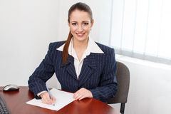 Brunette businesswoman write on blank paper Stock Photo