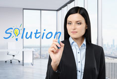 Brunette businesswoman is writing a word ' solution ' on the glass screen. Royalty Free Stock Image