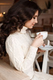 Brunette in a cafe drinking tea, eating sweets, reading a book, looking at the cup, beautiful eyes and gorgeous makeup Stock Images