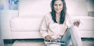 Brunette calculating with the tablet pc Royalty Free Stock Images