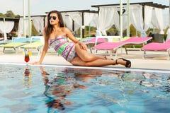 Brunette caliente con los vidrios de sol en cara de la piscina Foto de archivo libre de regalías