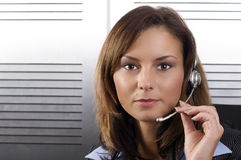 Brunette call operator. Young brunette call center agent talking on the headset in a modern office setting Stock Images