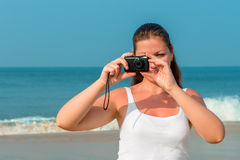 Brunette with a camera taking pictures Royalty Free Stock Images