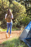 Brunette camper walking away from tent Stock Photography