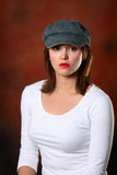 Brunette with cap red backdrop Stock Image