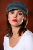 Brunette with cap red backdrop Stock Photography