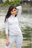Brunette in casual at pond Stock Photography
