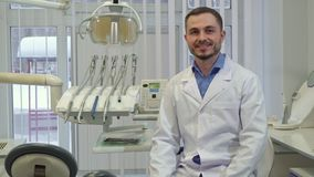 Dentist sits down on the chair at his office. Brunette caucasian dentist sitting down on the chair at his office. Middle aged male doctor smiling for the camera Stock Image