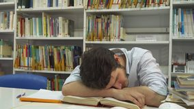 Guy sleeps at the library. Brunette caucasian guy sleeping at the library. Young bearded man getting tired at the table. Attractive male student wiping his eyes Royalty Free Stock Photo