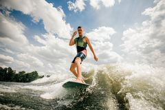 Brunette caucasian surfer performs his professional abilities. Active brunette caucasian surfer performs his professional abilities and skills, rides the waves Stock Images