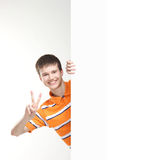 A brunette Caucasian teenage boy holding a banner. A smart brunette Caucasian teenage boy in an orange shirt holding a large white banner. The image is taken on royalty free stock image