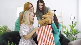 Brunette caucasiana esperando mulher que recebe ursinho de peluche de seus amigos Quatro meninas bonitas tendo uma festa de pré-p vídeos de arquivo