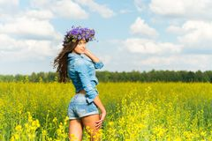 Brunette in chaplet in a yellow field Stock Photo