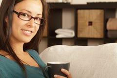 Brunette che mangia caffè. Colori caldi. Trucco di base. Fotografia Stock