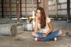 Brunette che si siede nel magazzino abbandonato (3) Immagine Stock