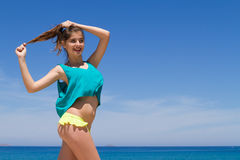 Brunette cheerful teenage in beachwear enjoys the Royalty Free Stock Photos