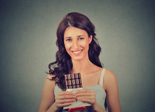 Brunette chocolate loving beauty. Happy woman with dark chocolate. Royalty Free Stock Image