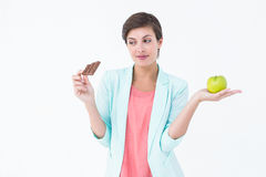 Brunette choosing between an apple and chocolate bar Royalty Free Stock Images