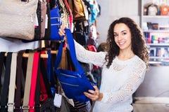Brunette choosing bag in store Stock Photography