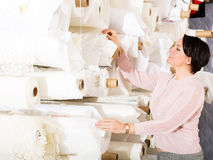 Brunette choosing fabric skeins. Smiling mature brunette choosing fabric skeins in textile shop stock photography