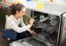 Brunette choosing new dish washing machine Royalty Free Stock Photo