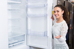 Brunette choosing new refrigerator royalty free stock photos