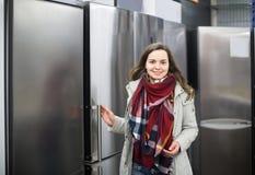Brunette choosing new refrigerator in hypermarket Royalty Free Stock Image