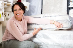 Brunette choosing sleeping mattress. Happy brunette choosing sleeping mattress in textile shop Stock Photography